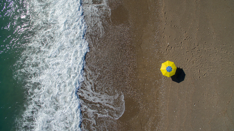 Droneshot: sunbathing on lara beach. No people only umbrella